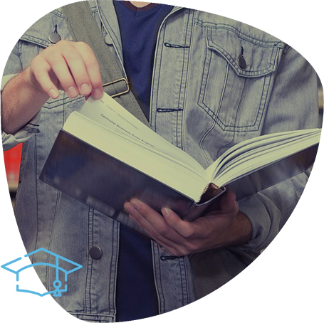 An image showing a person in denim jacket looking through a book